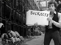 "Black-and-white still of Bob Dylan holding ""Suckcess"" sign in a back alley"