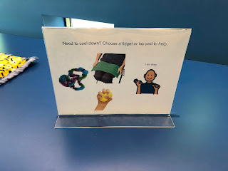 "sign on top of blue table saying ""Need to cool down? Choose a fidget or lap pad to help. There are also four images: fidget, person with lap pad, person saying ""I'm okay,"" and hand squeezing a yellow ball"