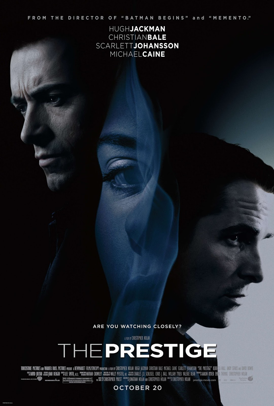The theatrical release poster for The Prestige. It depicts the faces of three of the stars. From left to right: Hugh Jackman, Scarlett Johansson and Christian Bale are shown. Jackman and Bale are both shown in black and white, while Johansson is partially obscured by a blueish-gray, translucent smoke.