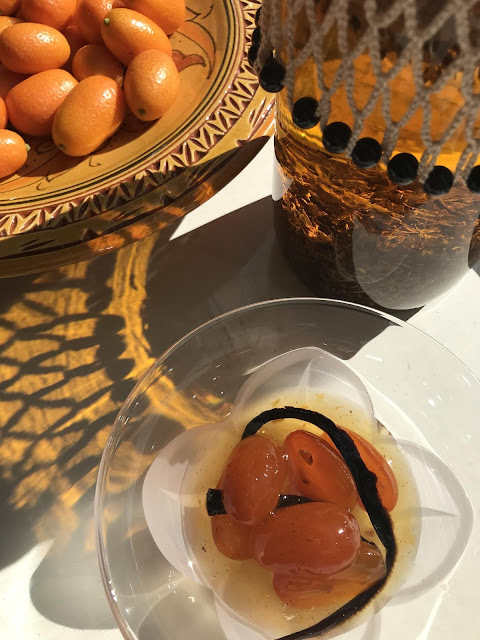 Preserved cumquats and fresh nagami fortunella and calendula infusing in olive oil photo