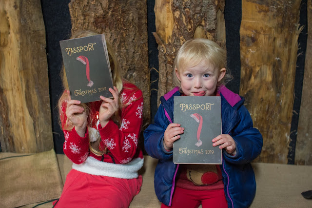 2 children holding booklets saying Passport to Christmas 2019 on from waiting at Passport Control at Marsh Farm