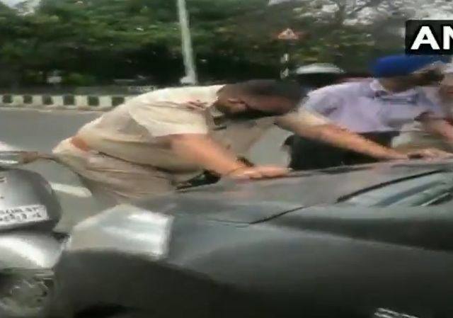 कोरोना के दौरान चेक पोस्ट पर पुलिस ने गाड़ी  रोका तो ड्राइवर ने बोनट पर घसीटा, देखें VIDEO