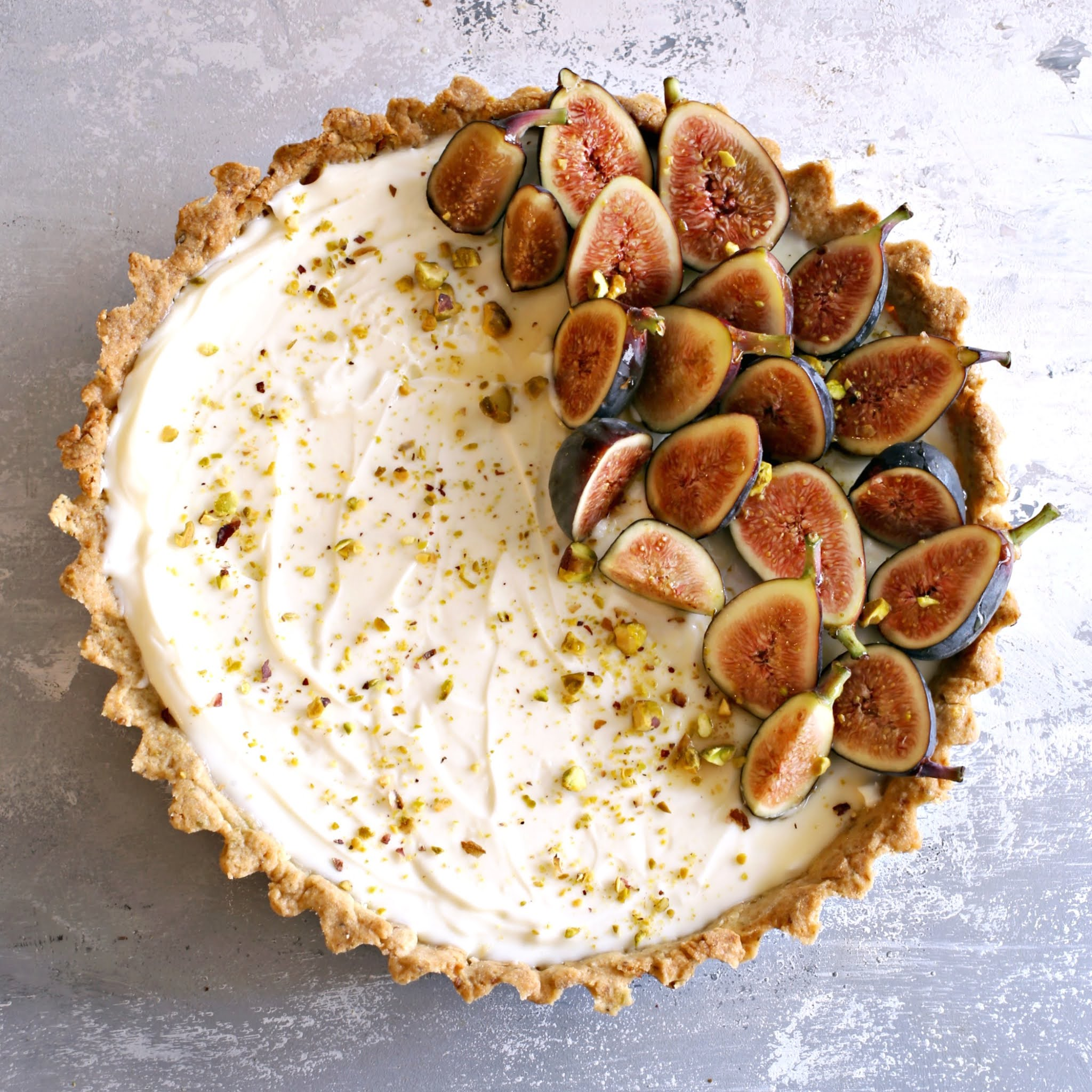 Recipe for a tart with pistachio crust, no-bake cheesecake filling and honey glazed figs.