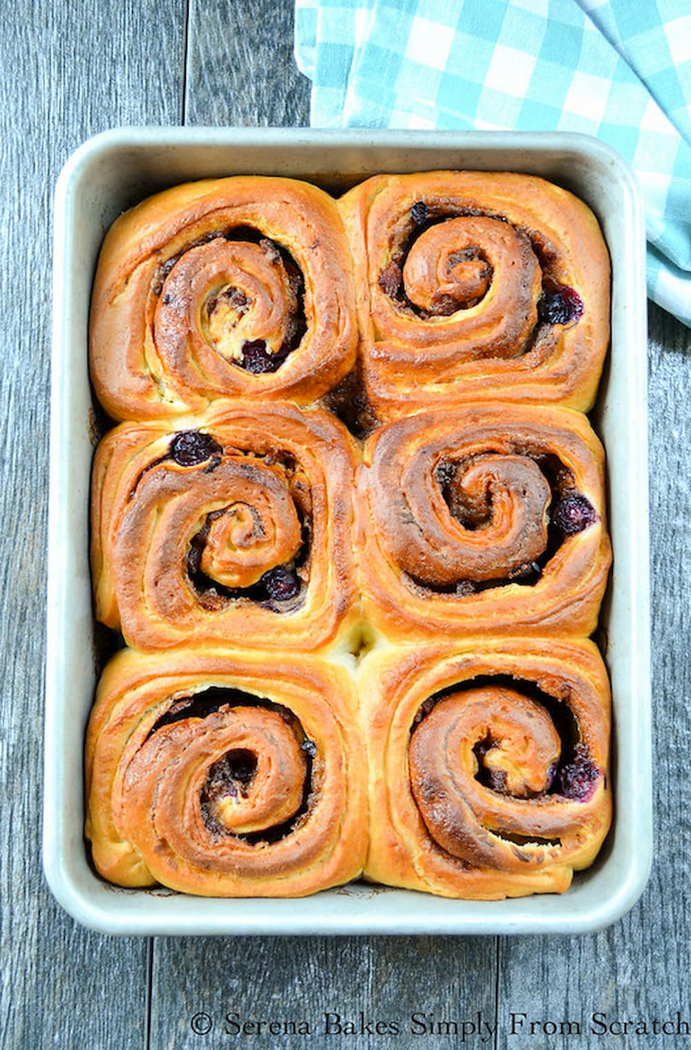 Down shot of Baked Blueberry Bacon Cinnamon Rolls in a baking pan.