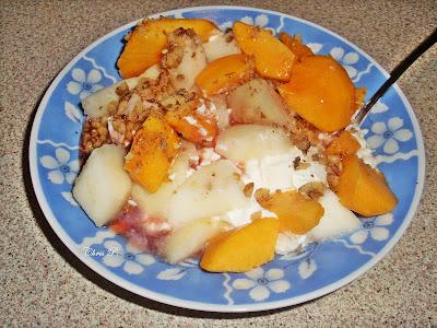Πιάτο βαθύ με γαλάζια σχέδια που έχει κομμάτια φρούτων,ροδάκινο,πεπόνι,μήλο,καρύδια,γιαούρτι και γλυκό κουταλιού.