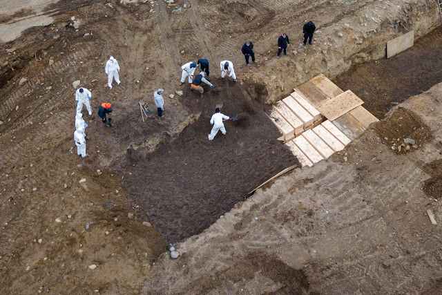 Drone footage showing NYC workers burying bodies in a mass grave on Hart Island