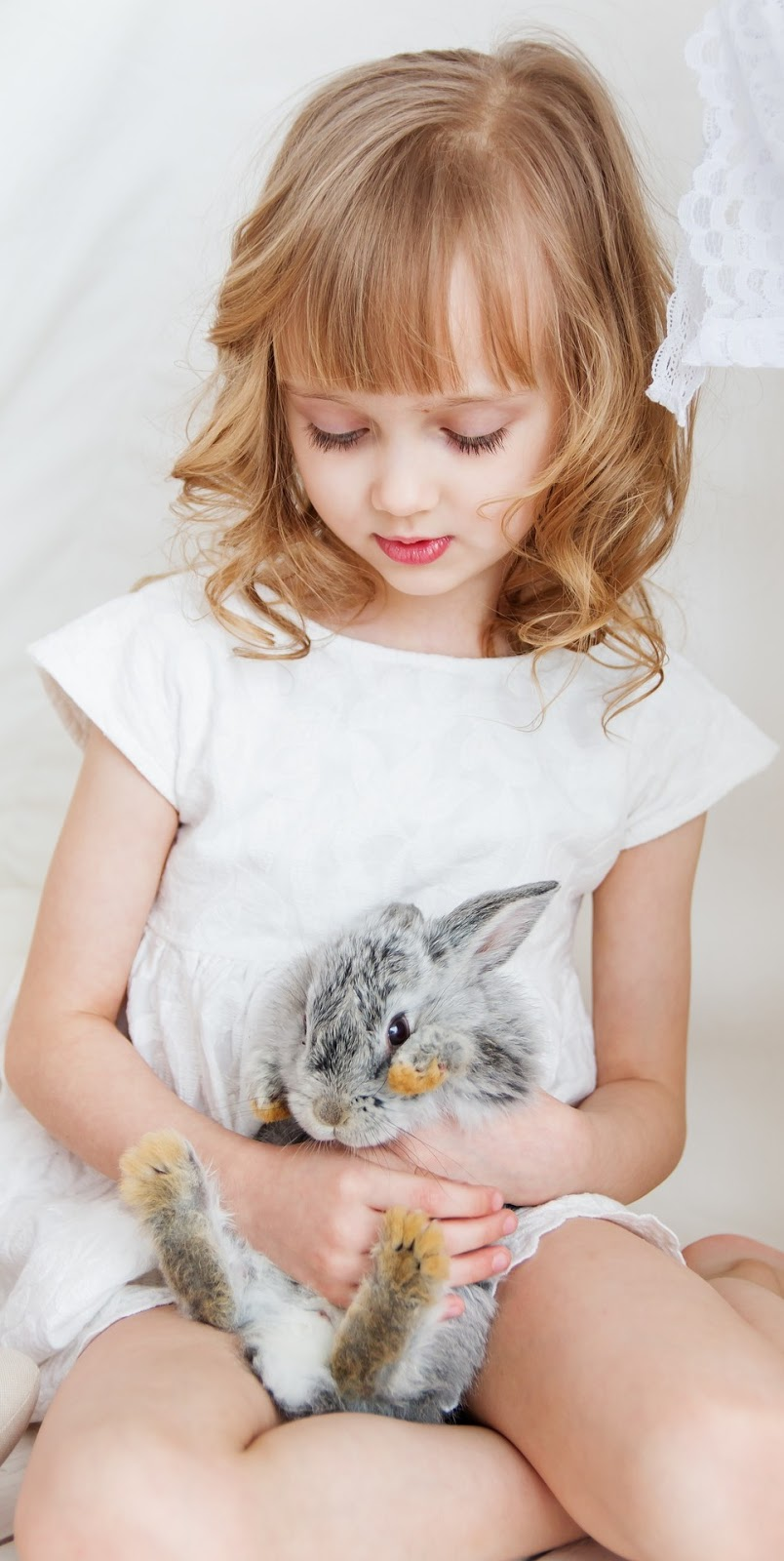 A young girl holding a cute rabbit.