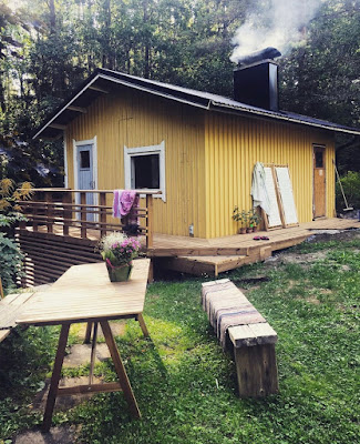 keltainen sauna, kaksi seinää kiertävä terassi sekä ruokapöytä nurmikolla