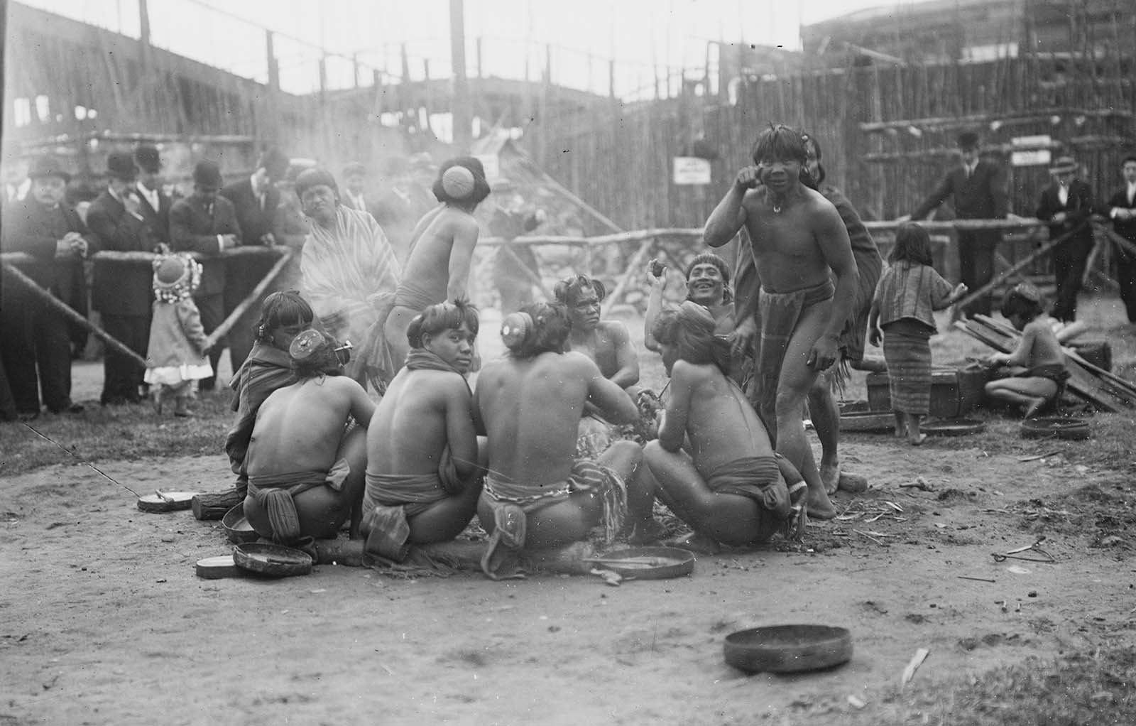 Filipinos are pictured in loin cloths sitting in a circle together at Coney Island in New York in the early 20th century while crowds of Americans watch on from behind barriers.
