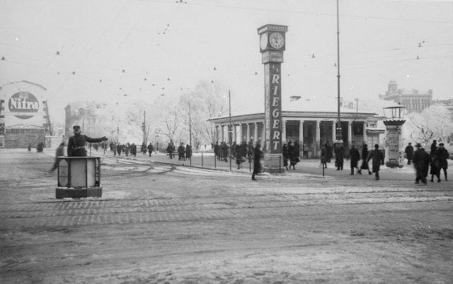 """1933 год. Рига. На углу бульвара Бривибас и Аспазияс. Часы с рекламой шоколадной фабрики """"Th. Riegert"""""""
