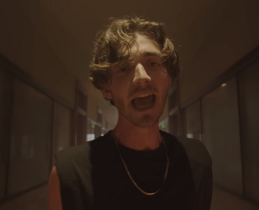 Greyson Chance cantando no clipe de Bad To Myself, com uma camiseta preta de mangas enroladas, parecendo uma regata