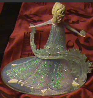 "image Frozen Inspired Handcrafted figurine captures Elsa in a dramatic pose, with crystalline snowflakes, 18 crystals, glitter and elegant mirror base. Measures 7-1/2"" H"