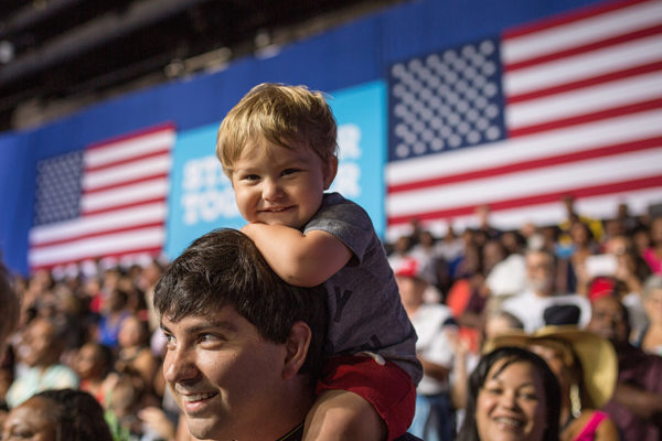 image of a little white boy sitting on his dad's shoulders