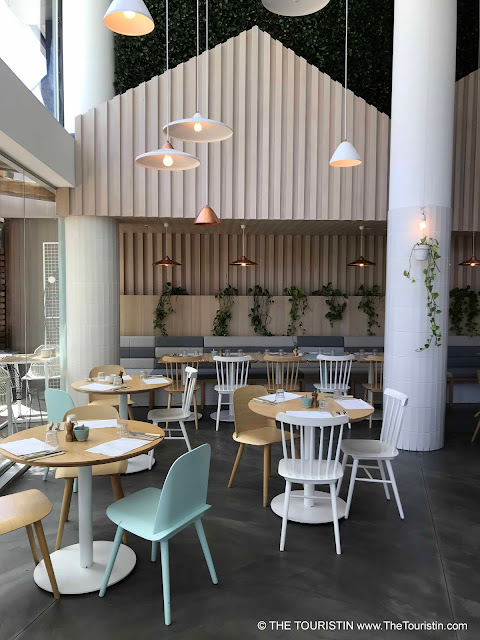 Cafe with pastel green and white chairs on wooden tables on concrete flooring. White lamps. hanging from a high ceiling