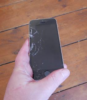 A hand holding a broken phone.