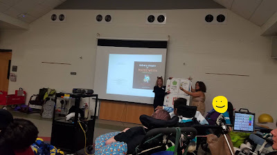 room of young adult students in wheelchairs with two librarians at the front of the room reading adapted book on large white board