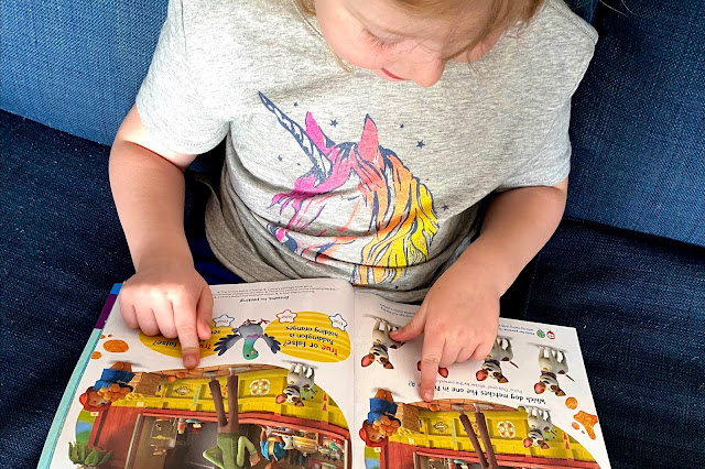A child pointing at 2 images and showing one of the differences in a spot the difference activity