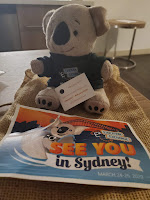 Stuffed koala and a postcard that says See You in Sydney