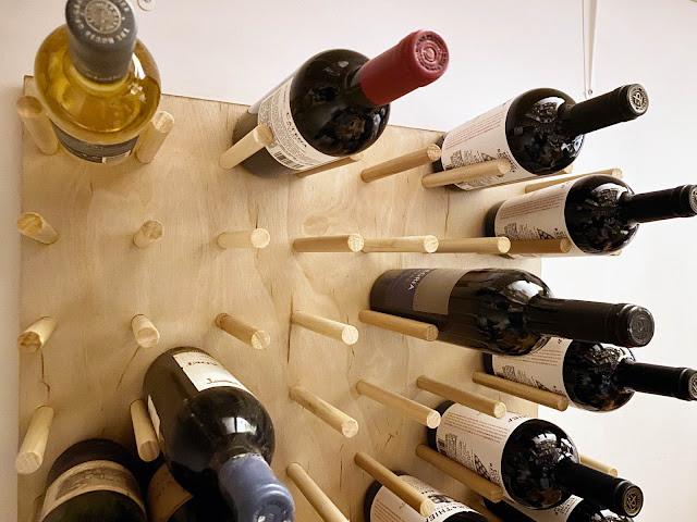 organized wine bottles on pegboard rack