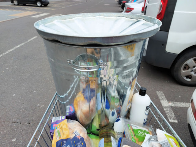 A shopping trolley containing groceries and a shiny metal incinerator