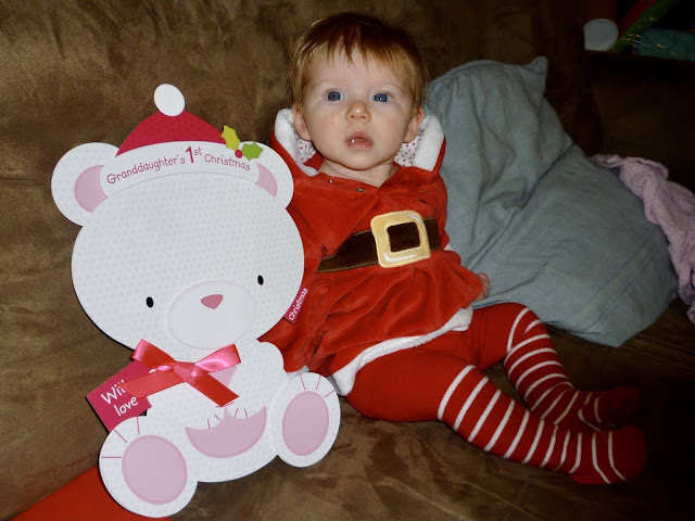"A 3 month old propped up on a sofa in a christmas dress and striped tights next to an oversized  bear shaped card saying ""Grandaughters first Christmas"""