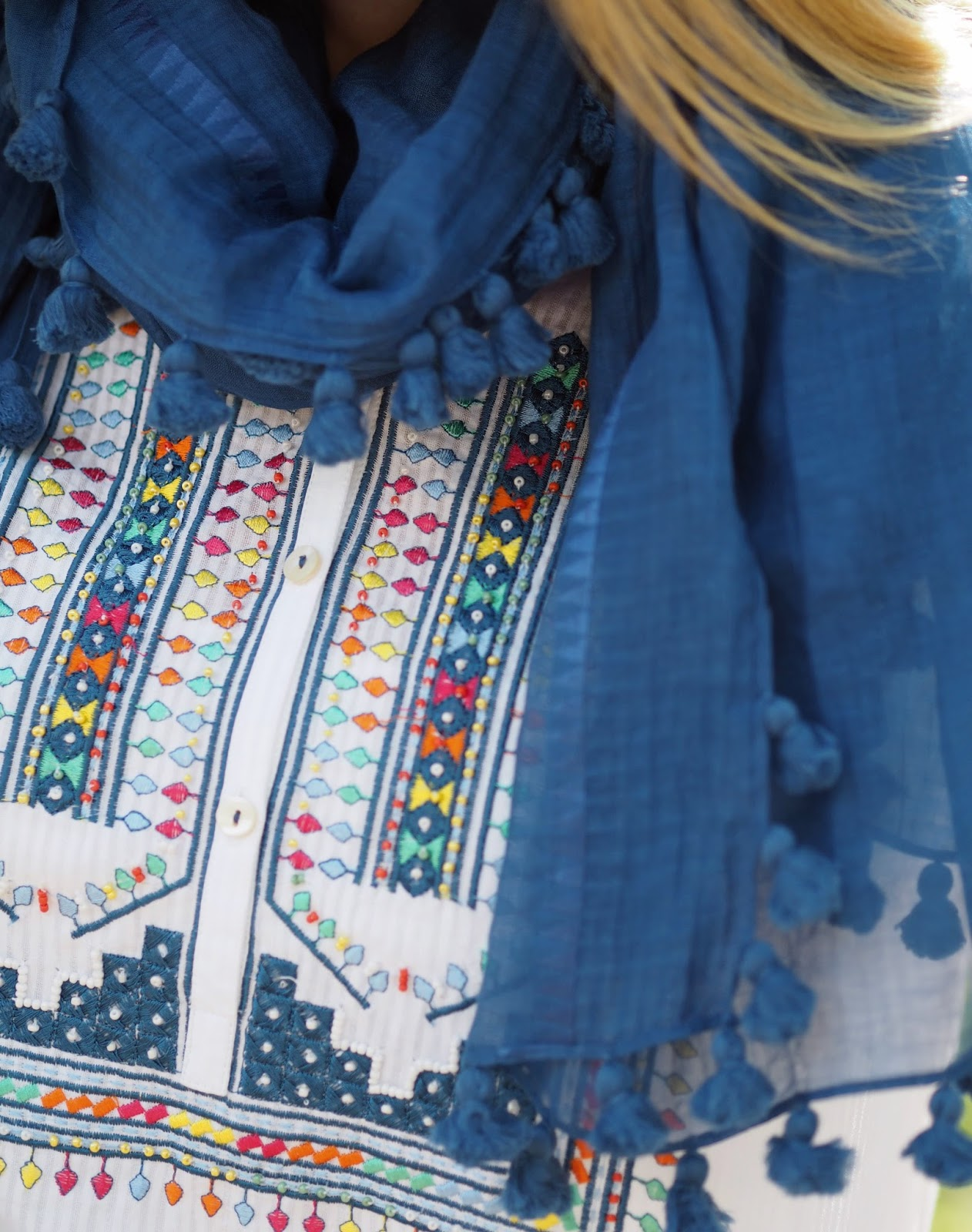 Multi-coloured embroidery on white top with blue pompom scarf