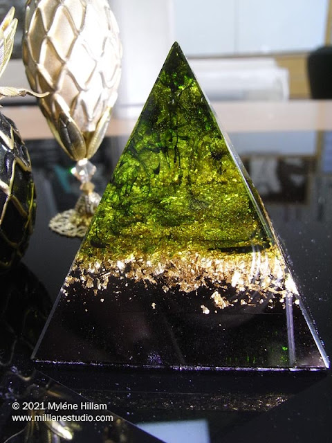 resin pyramid filled with layers of avocado, gold metal leaf and black resin sitting on a glossy black table