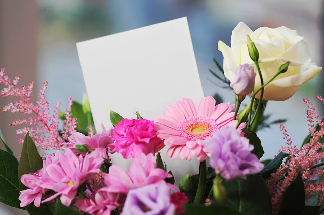 A bouquet of pink and white flowers in a vase. This would make a great gift idea, especially for women!
