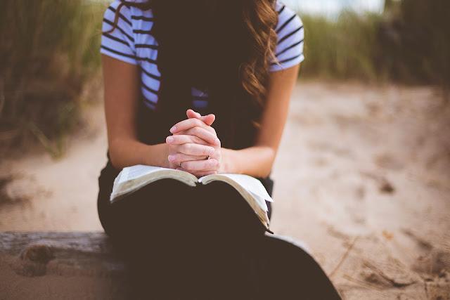 Moça lendo a bíblia ao ar livre
