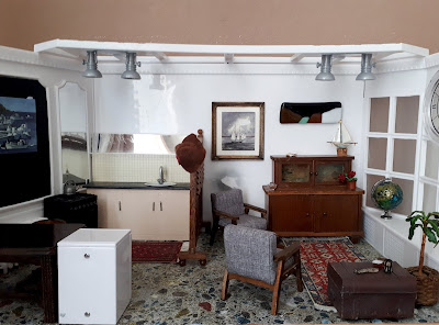 1/12 scale modern miniature scene of a single man's flat, with a simple kitchen on the left with a large vintage table and captain's chair, and a living room on the right with two mid-century modern armchairs, an antigue cupboard, battered sailor's chest and afghan rug.