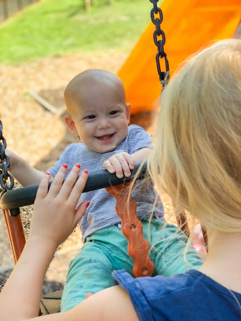 baby boy being pushed on a swing by his biggest sister. He is smiling
