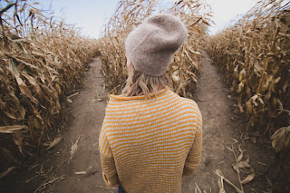 woman in a field looking at two different paths