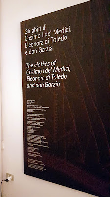 black plate with white text about the clothes of cosimo I, Eleonora di Toledo and don Garzia