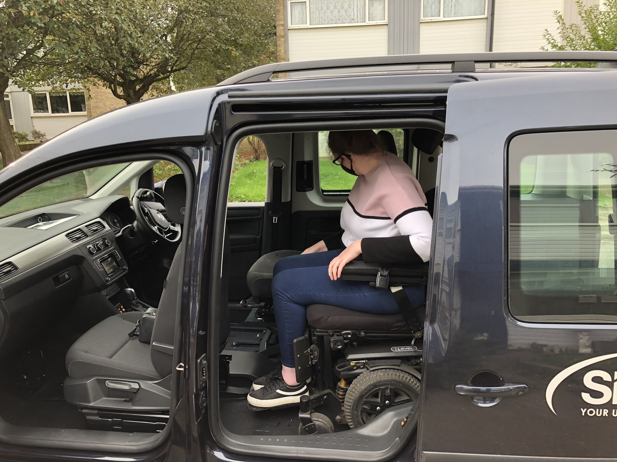 Shona, a young white woman, is sat in her powerchair inside a wheelchair accessible vehicle. She is wearing a face mask with her face turned away from the camera.