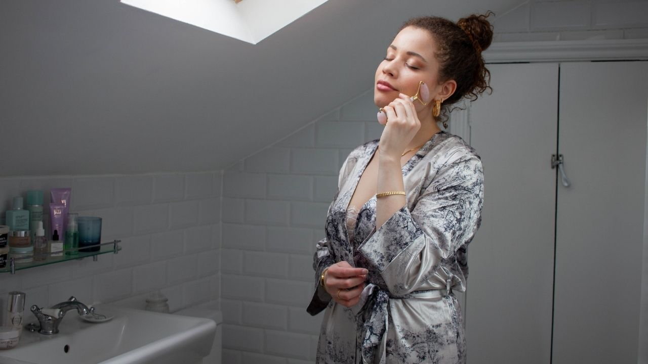 This is an image of Eboni (eboniivoryblog) standing in a bright bathroom using a rose quartz roller on her left cheek. She is wearing a silk Dior-inspired dupe robe.