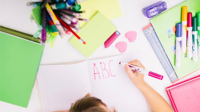 criança escrevendo em caderno com canetas coloridas