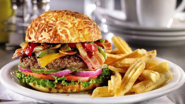 a tall hamburger with all the fixins along with french fries