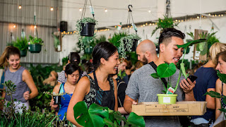 A group of people milling around hanging plants and plants on tables.