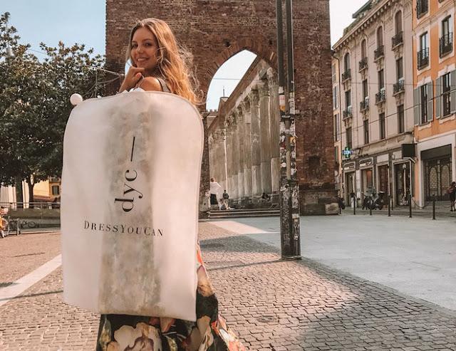 Foto di una modella con in mano un abito noleggiato da DressYouCan