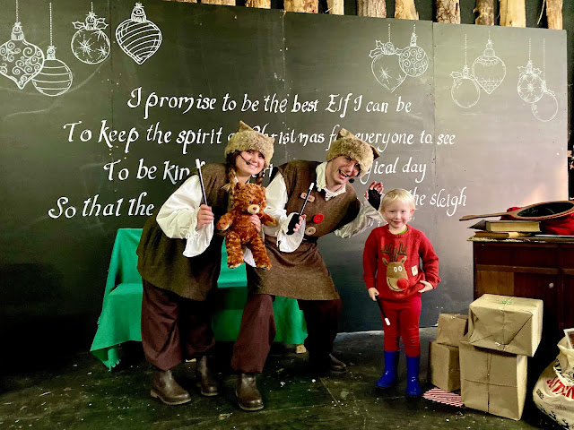 A 3 year old on stage posing for a photograph with 2 elves at Marsh Farm Father Christmas Experience while visiting for a review
