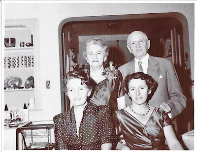Richard and Alice Neumann, looking somewhat older, stand with two young women in their home. Everyone is well-dressed. Black and white.