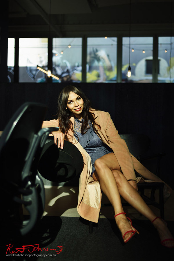 Smiling portrait of a seated model in a long coat with beautiful long legs in direct light for a modelling portfolio. Photographed by Kent Johnson, Sydney, Australia.
