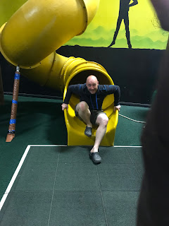 man coming out slide indoor play area