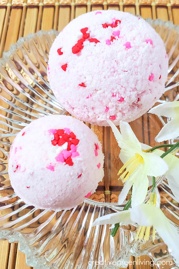 Learn how to make easy DIY bath bombs with essentials oils that smell like candy hearts! These step by step instructions and video makes it simple for beginners to learn how to make bath bombs to give as gifts, keep or to sell. You'll love using natural ingredients like epsom salt to get a Lush quality bath bomb for a lot less money. #creativegreenliving #bathbomb #howtomakebathbombs