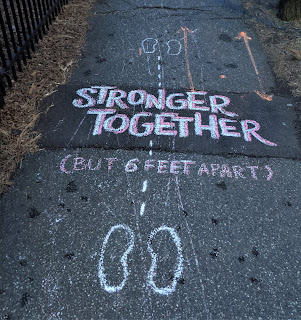 "A sidewalk with chalk that says in bold lettering:  ""Stronger Together But 6 Feet Apart."""