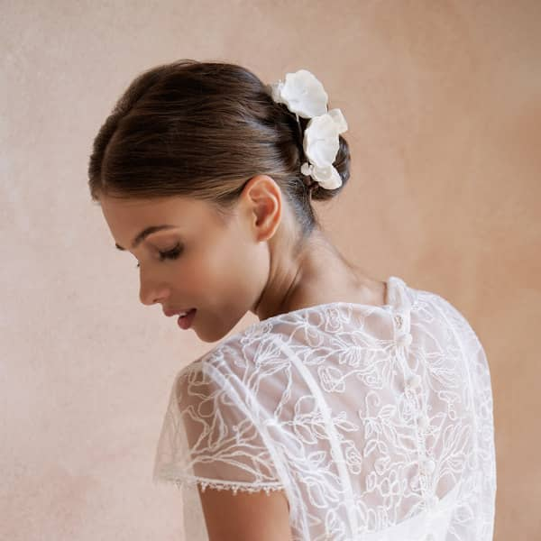 bride wearing paper flower accessory on chignon