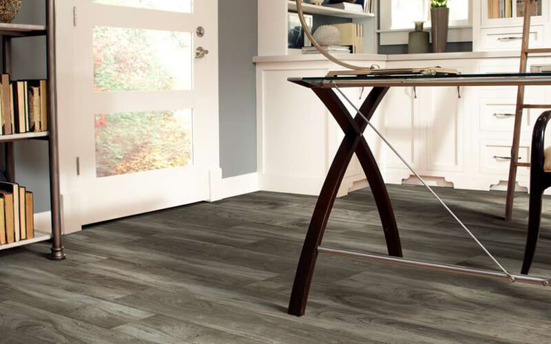 Drafting table in an office with driftwood-brown hardwood-look flooring