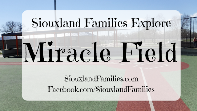 "in background, a red and green rubber baseball field with white painted lines at Miracle Field in Riverside Park in Sioux City, Iowa. In foreground, the words ""Siouxland Families Explore Miracle Field"""