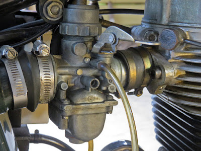 Close-up of motorcycle carburetor.