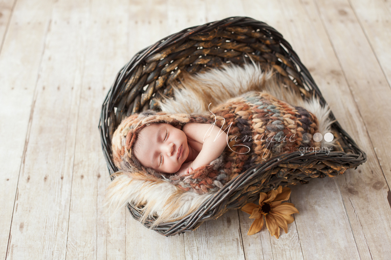 Newborn boy wrapped up in a cocoon lying on cozy fur
